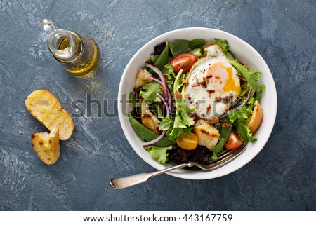 Breakfast salad with toasted bread, eggs and bacon