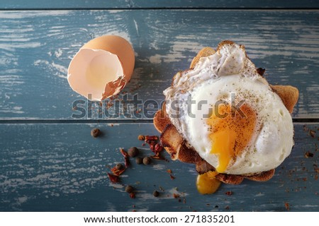 Breakfast - sandwich with fried egg and bacon over blue wooden table - stock photo