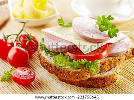 breakfast sandwich with sliced sausage and tomato on kitchen table - stock photo