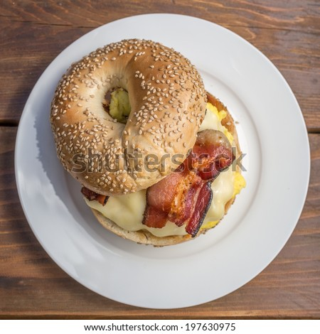 Breakfast sandwich with toasted sesame bagel, egg, bacon and cheese.