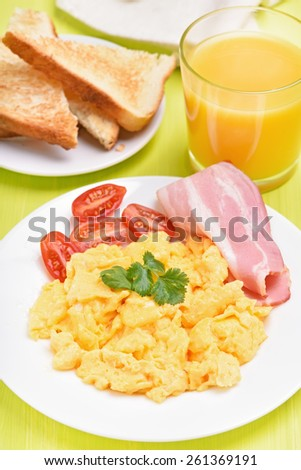 Breakfast scrambled eggs with bacon, tomatoes and orange juice - stock photo