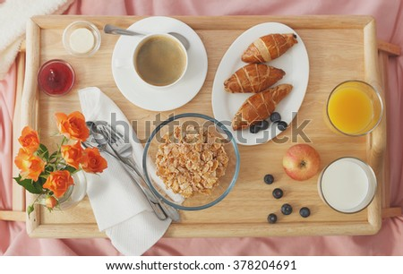 breakfast served in bed on wooden tray. Low contrast