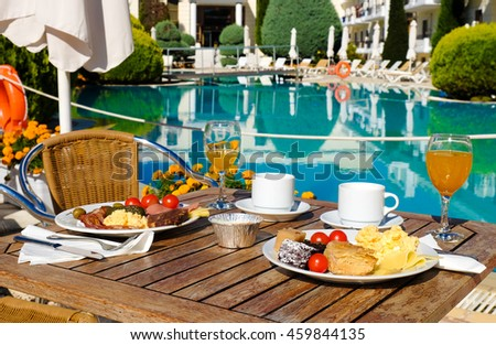 Breakfast served near the pool at standard Hotel, restaurant or pension in Greece - stock photo