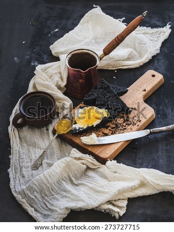 Breakfast set. Coffe, black toasts with cream-cheese and orange marmalade on dark grunge table surface, top view - stock photo