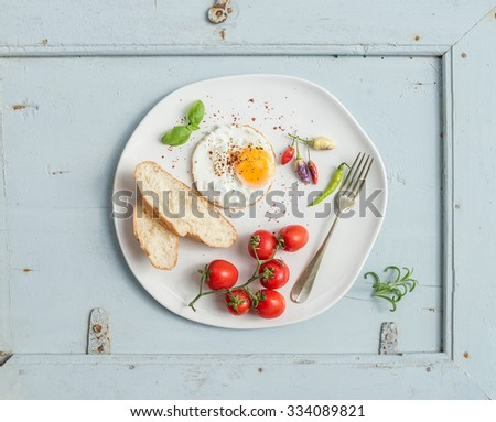 Breakfast set. Fried egg, bread slices, cherry tomatoes, hot peppers and herbs on white ceramic plate over light blue wooden backdrop, top view - stock photo