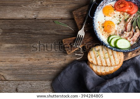 Breakfast set. Pan of fried eggs with bacon, fresh tomato, cucumber, sage and bread on rustic serving board over wooden background, top view, copy space - stock photo