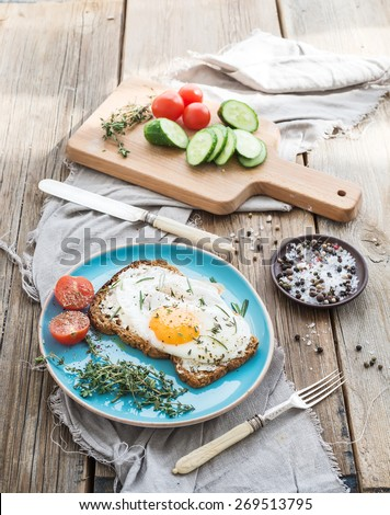 Breakfast set. Whole grain sandwich with fried egg, vegetables and herbs on rustic wooden table, morning mood, top view - stock photo