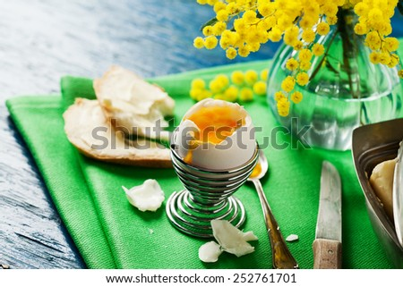 Breakfast setting with open soft boiled egg in egg cup - stock photo