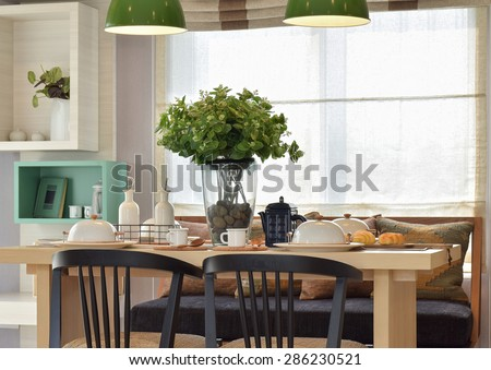 Breakfast setup on wooden table with nice vase and modern chair - stock photo