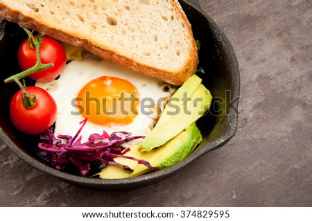 Breakfast skillet pan of fried egg, avocado and tomato. Served on a gray stone slate background. - stock photo