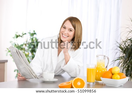 Breakfast - Smiling woman reading newspaper in kitchen, with coffee and fresh orange juice - stock photo