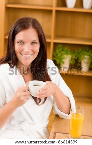 Breakfast - Smiling woman with cup of coffee in modern interior