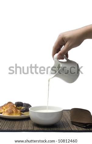 Breakfast: some croissants and one hand pouring milk in the bowl