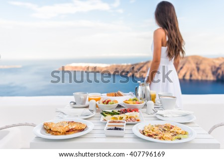 Breakfast table and luxury travel woman on santorini. Well balanced perfect breakfast table served at resort. Female tourist is looking at beautiful view of sea and caldera enjoying her vacation. - stock photo