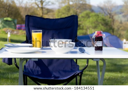 Breakfast table set up outdoors on Welsh camp site on a summers morning  in rural Wales - stock photo