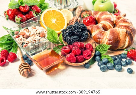 Breakfast table setting with croissants, muesli, fresh berries, fruits orange, apple, milk. Healthy nutrition. Retro style toned - stock photo