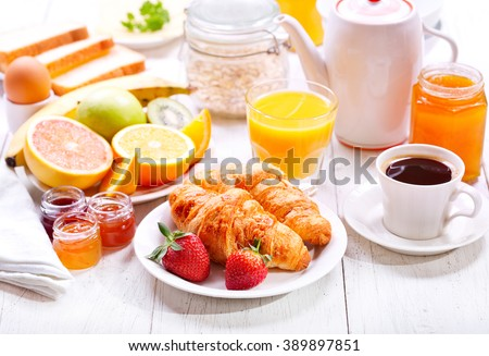Breakfast table with croissants, coffee, orange juice, toasts and fruits