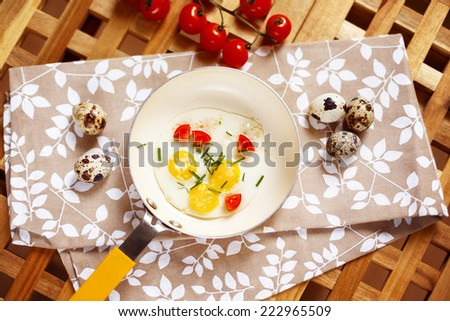 Breakfast table with fried eggs pan. Quail eggs, little yellow frying pan, cherry tomatoes served on wooden table. Top view. - stock photo