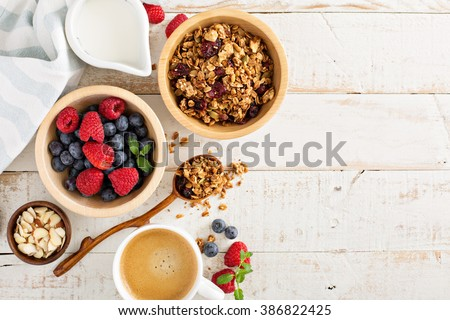 Breakfast table with granola, coffee and fresh berries - stock photo