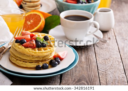 Breakfast table with stack of waffles and fresh berries - stock photo
