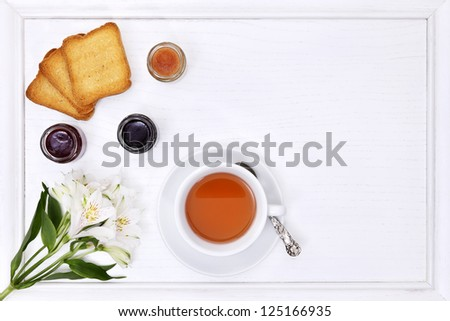 breakfast table with tea, cup of tea, flower,  jam and bread