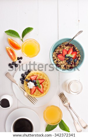Breakfast table with waffles, granola and fresh berries - stock photo
