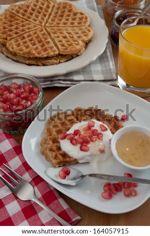 Breakfast table with whole grain waffles, fruit and orange juice - stock photo