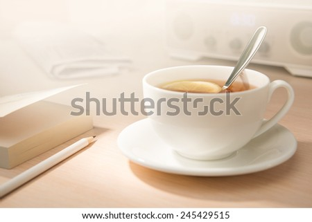 Breakfast. Tea, notebook, pencil, newspaper - stock photo