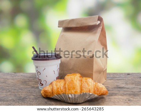 Breakfast to go,coffee and croissant with paper bag on wooden table over green defocused background - stock photo