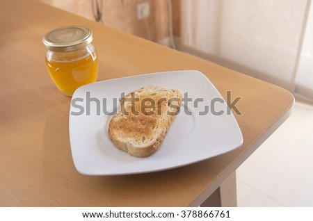 Breakfast. Toast with a jar of honey on a white plate with natural light on a table.  - stock photo