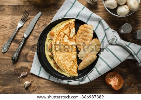 Breakfast top view. Delicious and healthy breakfast with omelette, tomatoes and sliced bread in a frying pan. - stock photo
