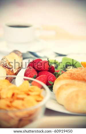 Breakfast tray. Continental breakfast tray with coffee, cornflakes, croissant, strawberries, kiwi and bread. Shallow depth of field. - stock photo
