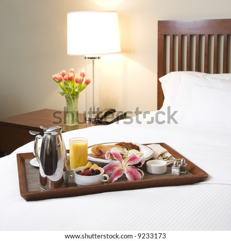 Breakfast tray laying on white bed in upscale hotel. - stock photo