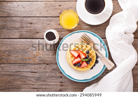 Breakfast waffles with fresh berries stacked on a plate - stock photo