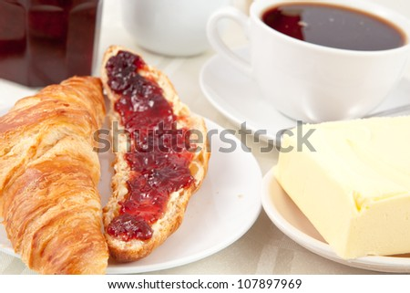 Breakfast with a croissant spread with jam indoors