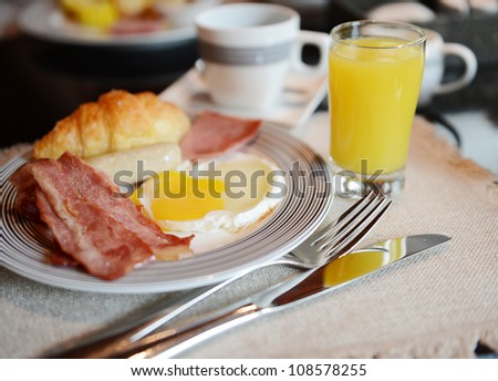 Breakfast with bacon, fried egg, orange juice and coffee. - stock photo