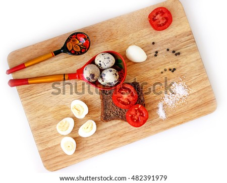 Breakfast with boiled quail eggs and wholegrain bread on board flat lay, russian painted wooden spoons