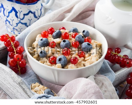 Breakfast with bowl of oatmeal porridge with blueberries and red currants on a kitchen napkin on a wooden tray