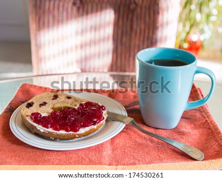 Breakfast with coffee and  a slice of bagel with cream cheese and lingonberry jam. - stock photo