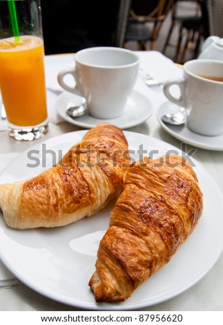 Breakfast with coffee and croissants in a basket on table