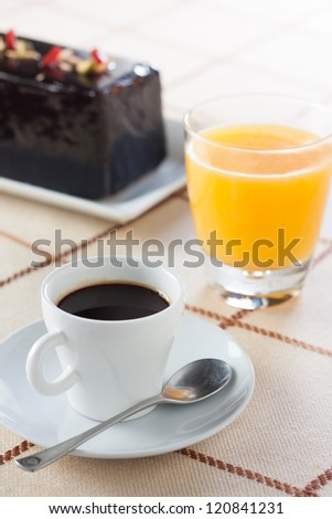 Breakfast with coffee, orange juice and chocolate plumcake
