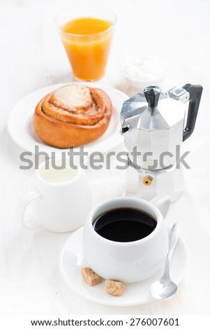 breakfast with coffee, sweet bun, cream and orange juice, top view, vertical
