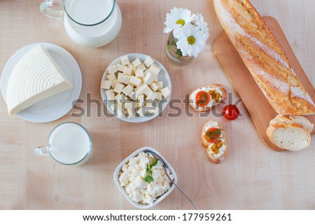 Breakfast with cottage cheese, glass of milk, bulgarian cheese and sandwiches, on white wooden table - stock photo