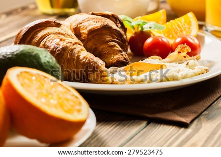 Breakfast with croissant, eggs end orange juice - stock photo