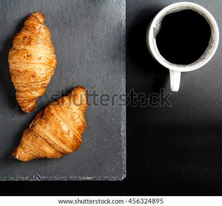 Breakfast with croissants, black coffee on granite stone plate black background. Flat lay, top view - stock photo
