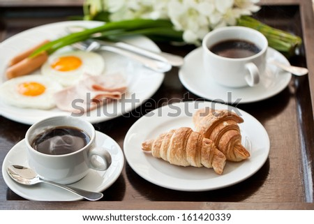 breakfast with cup of black coffee, eggs and croissants on balcony