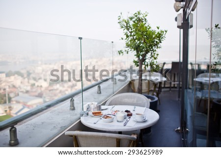 breakfast with cup of black coffee, musli and yoghurt on balcony - stock photo