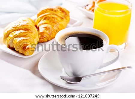 breakfast with cup of coffee, croissants and orange juice