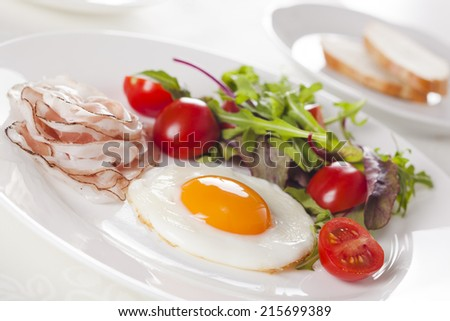 Breakfast with eggs, ham and fresh salad. - stock photo