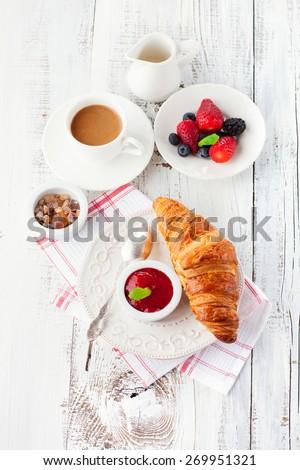 Breakfast with fresh croissants, cup of coffee and strawberry jam on a white wooden background, top view - stock photo